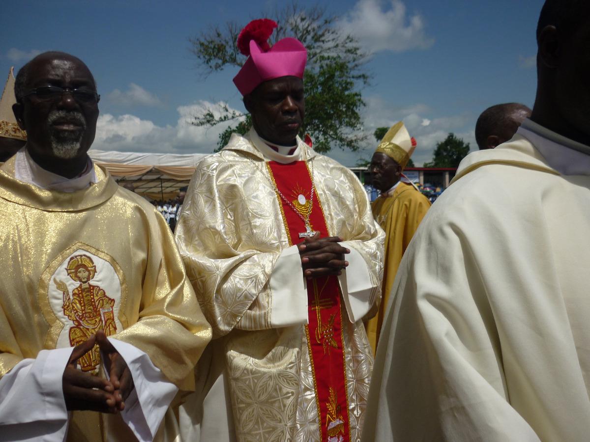 La cérémonie a lieu en plein air, au stade, Mgr Georges s'avance avec le Vicaire Général.