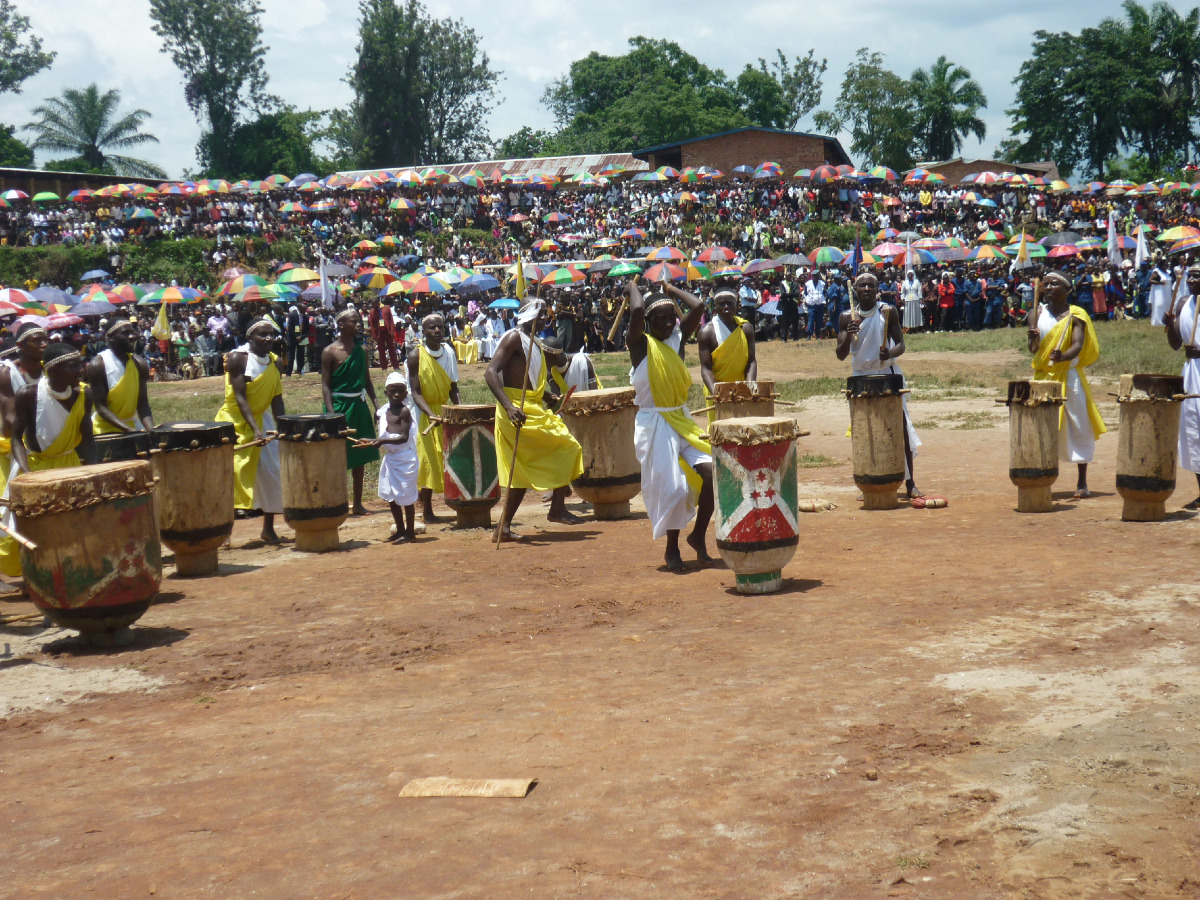 Les tambourinaires acclament et dansent pour le nouvel évêque. Derrière la foule des fidèles.