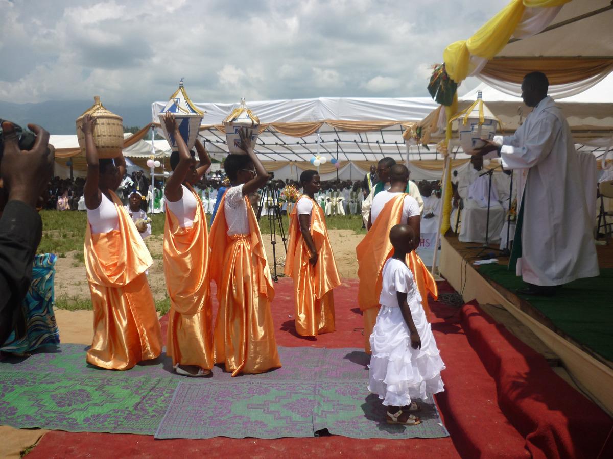 Procession des offrandes : ciboires et calices portés dans des paniers par des femmes en beaux pagnes.