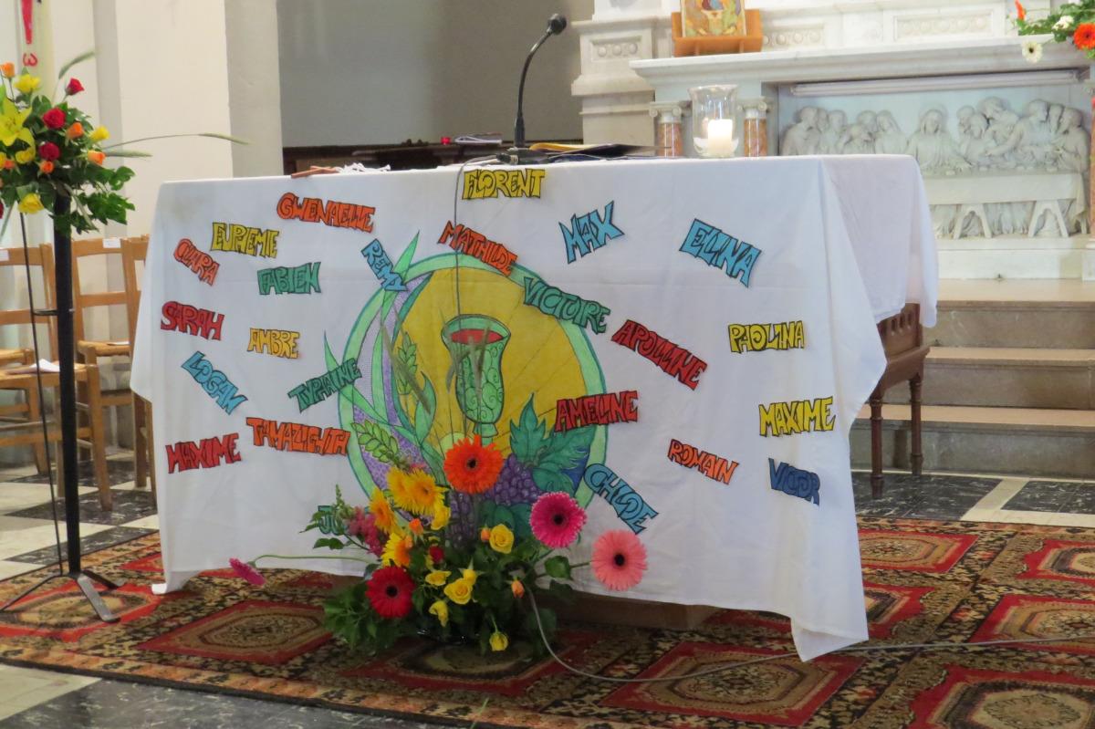 Les prénoms des communiants écrits sur la nappe de la table eucharistique