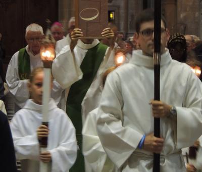 Maxence, séminariste, porte la croix de procession