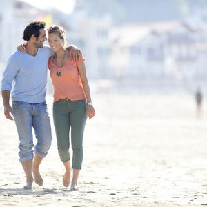 Middle-aged couple walking on the beach
