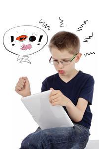 enfant râlant en jouant sur une tablette informati