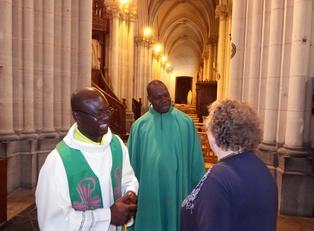 Pères C. Sanon, M. séri avec une paroissienne de la basilique sainte Maxellende