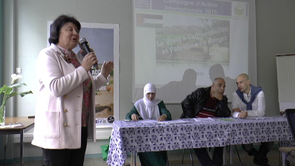 présente les participants à cette conférence organisée par le Secours Catholique, tandis que Isham traduit pour Jehad