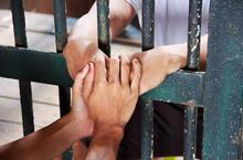 Gros plan mains barreaux prison