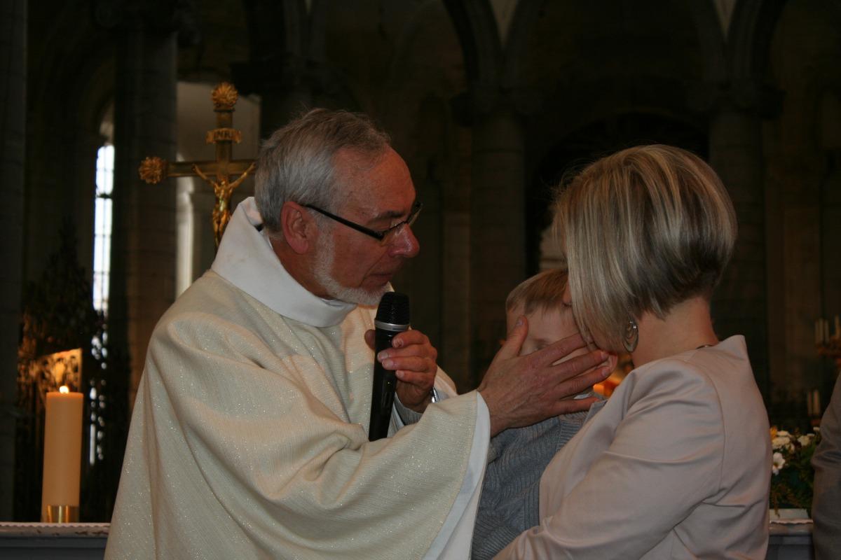 L'abbé Merville marque du signe de la croix un des