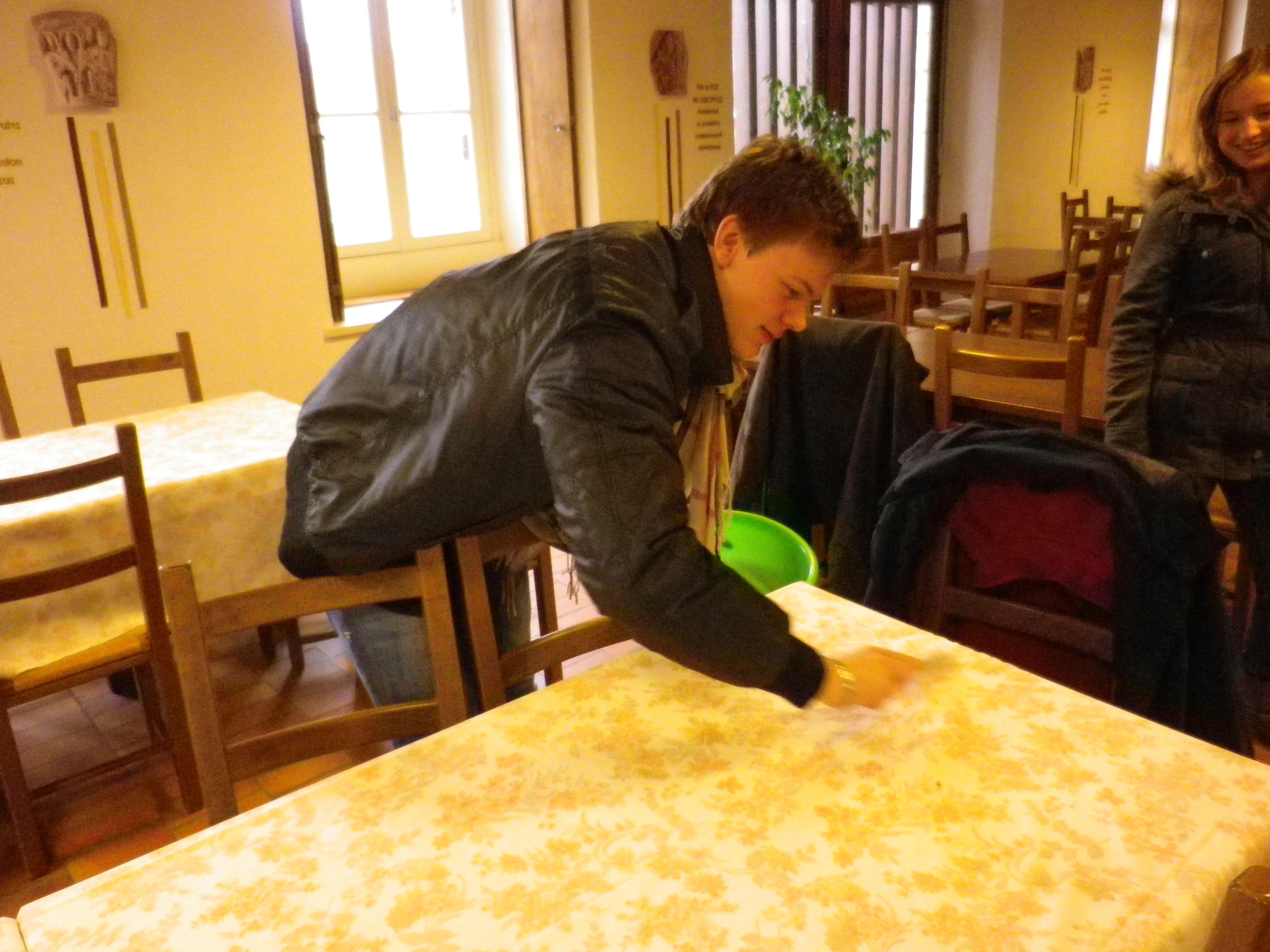 Sébastien nettoie une des tables.