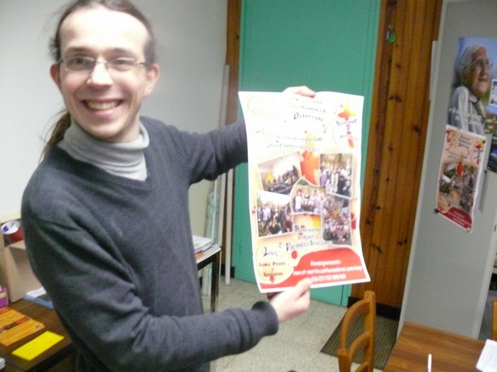 """Jean-François, animateur, présente l'affiche """"pub"""" de l'aumônerie"""