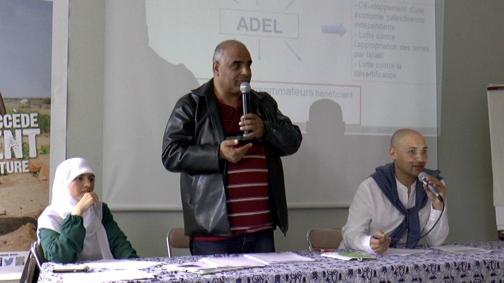 entouré de ses deux traducteurs, présente le projet innovant de l'association ADEL