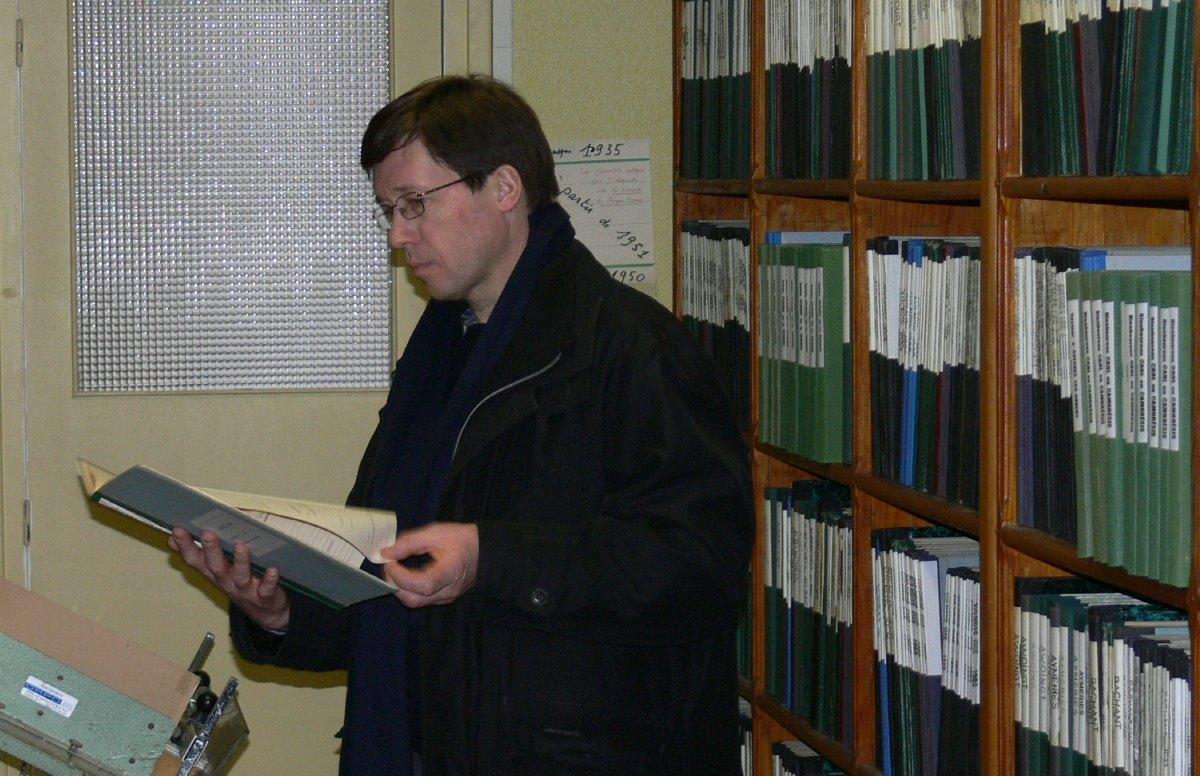 Christophe consulte le registre de son baptême.