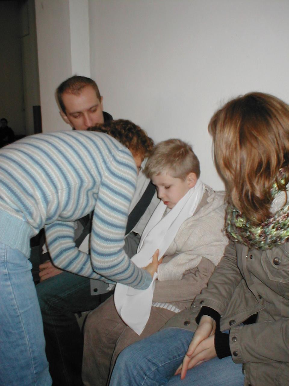 enfant enfilant le vêtement blanc du baptême